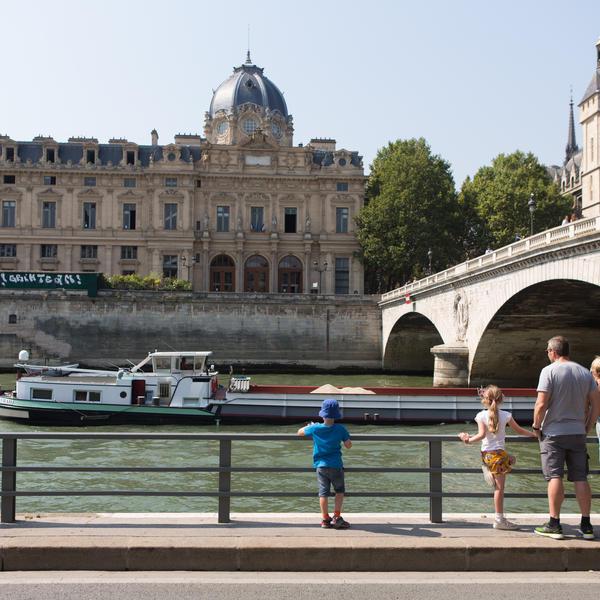 Une famille regarde passer une péniche sur la Seine